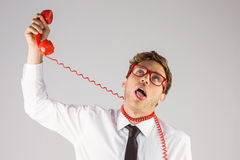 Geeky businessman strangling himself with telephone Stock Image