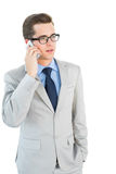 Geeky businessman talking on cellphone Stock Photography