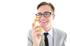 Geeky businessman talking on retro phone Stock Images