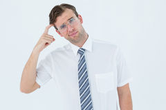 Geeky businessman thinking with finger on temple Stock Photo