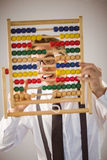 Geeky businessman using an abacus Stock Image