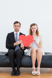Geeky couple sitting on couch Stock Photo