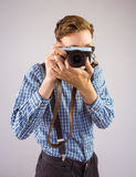 Geeky die hipster een retro camera houden Stock Afbeelding