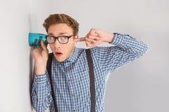 Geeky Geschäftsmann, der mit Schale heimlich zuhört Lizenzfreie Stockfotos