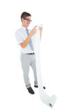 Geeky happy businessman reading a long receipt Stock Photos