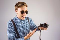 Geeky Hippie, der eine Retro- Kamera hält Lizenzfreie Stockfotografie