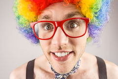 Geeky hipster in afro rainbow wig. On grey background Stock Photography