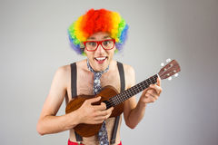 Geeky hipster in afro rainbow wig playing guitar. On grey background Royalty Free Stock Photo