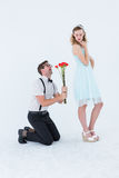 Geeky hipster begging his girlfriend taking roses. On white background stock photography