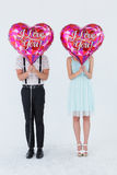 Geeky hipster couple with balloons in front of their head Royalty Free Stock Image