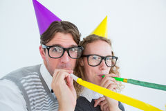 Geeky hipster couple blowing party horn Stock Photo