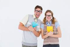Geeky hipster couple holding books and smiling at camera Royalty Free Stock Images