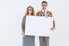 Geeky hipster couple holding poster Royalty Free Stock Images
