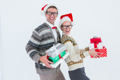 Geeky hipster couple holding presents Royalty Free Stock Photography