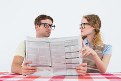 Geeky hipster couple reading newspaper Stock Photography