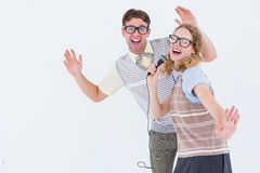 Geeky hipster couple singing into a microphone Stock Images