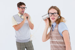 Geeky hipster couple speaking with tin can phone Stock Image