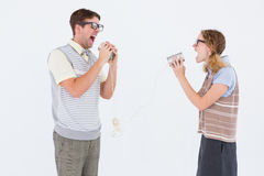 Geeky hipster couple speaking with tin can phone Royalty Free Stock Image