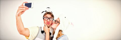 Geeky hipster couple taking selfie with smartphone. On white background Royalty Free Stock Image