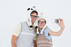 Geeky hipster couple taking selfie with smartphone Stock Image