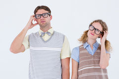 Geeky hipster couple thinking with hand on temple Royalty Free Stock Image