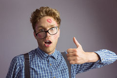 Geeky hipster covered in kisses Stock Photo