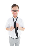 Geeky hipster fixing his tie smiling at camera Royalty Free Stock Images