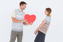 Geeky hipster giving heart card to his girlfriend Stock Photo