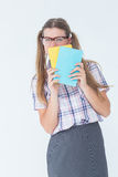 Geeky hipster hiding her face behind notepad Royalty Free Stock Photo