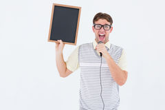 Geeky hipster holding blackboard and singing into microphone Stock Photo