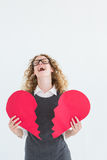 Geeky hipster holding a broken heart card Royalty Free Stock Photography