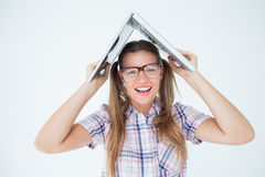 Geeky hipster holding her laptop over her head Stock Photo
