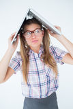 Geeky hipster holding her laptop over her head Stock Photography