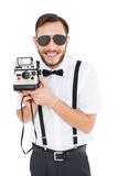 Geeky hipster holding a retro camera Royalty Free Stock Photo