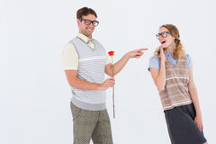 Geeky hipster holding rose and pointing his girlfriend Stock Photos