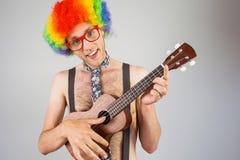 Geeky hipster i den afro regnbågeperuken som spelar gitarren Arkivbilder