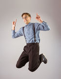 Geeky hipster jumping and pointing Stock Images