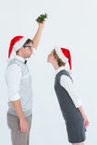 Geeky hipster kissing under mistletoe Royalty Free Stock Photography