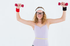 Geeky hipster lifting dumbbells in sportswear Stock Photography