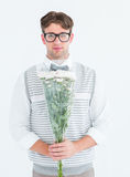 Geeky hipster offering bunch of flowers. On white background Royalty Free Stock Photos