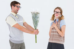 Geeky hipster offering flowers to his girlfriend Stock Image