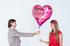 Geeky hipster offering red heart shape balloon to his girlfriend Royalty Free Stock Photo