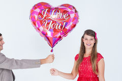 Geeky hipster offering red heart shape balloon to his girlfriend Royalty Free Stock Photos