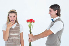 Geeky hipster offering red roses to his girlfriend Stock Images