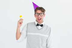 Geeky hipster in party hat with horn Royalty Free Stock Images