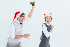 Geeky hipster running away from a man with mistletoe Stock Photos