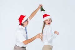 Geeky hipster running away from a man with mistletoe Royalty Free Stock Images