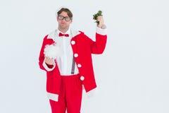 Geeky hipster in santa costume beard and mistletoe Stock Photo