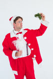 Geeky hipster in santa costume holding mistletoe Stock Photo