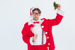 Geeky hipster in santa costume holding mistletoe Stock Photos